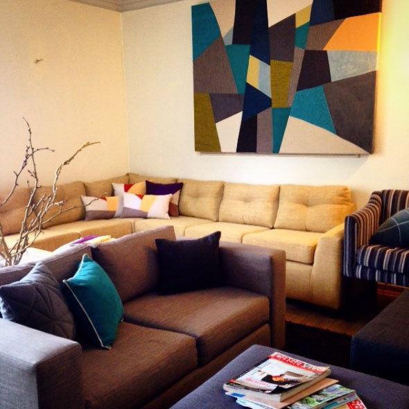 sala de ventas de la tienda livingstore en santiago con sofa esquinero amarillo y sofa dos cuerpos café un cuadro mosaico de tela en la pared
