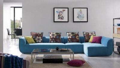 Sofa en L color azul con cojines decorativos