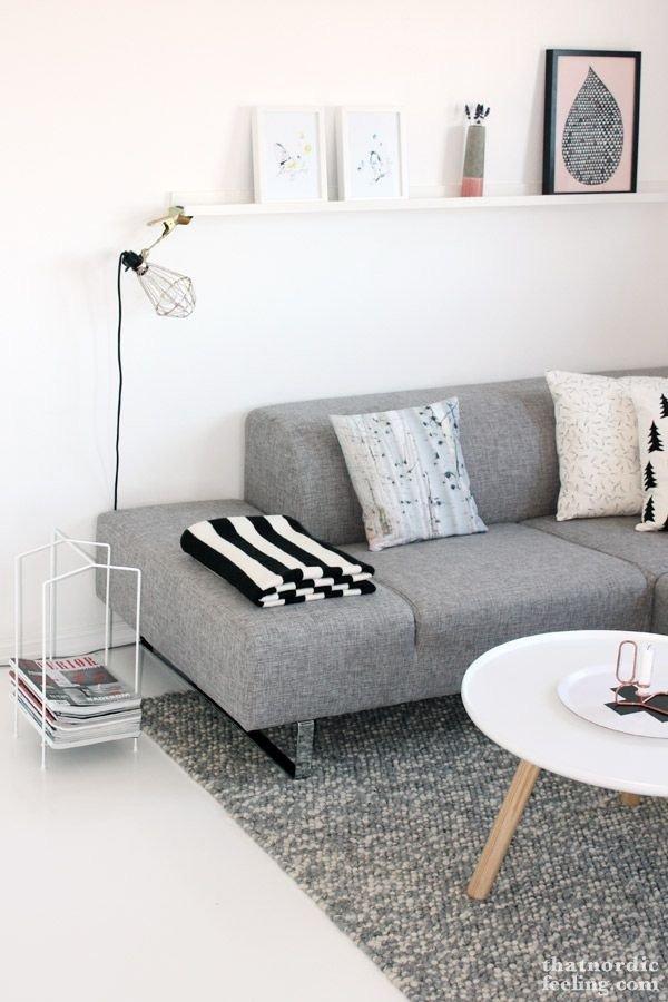 Sofá moderno sin brazos con patas metálicas en un hogar con alfombra y decoración minimalista