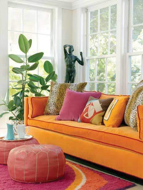 Sofá estilo marsala, tonos fuertes y vivos color naranja con alfombra moderna y juego de pouf con tapiz estampado oriental plantas adornando y cojines decorativos