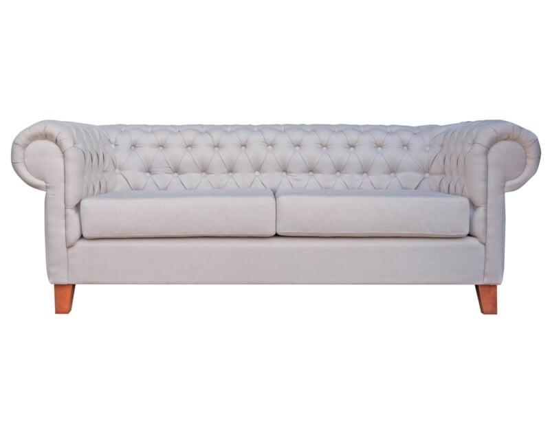 Elegante sofá modelo Chesterfield tapiz color perla y patas madera nogal