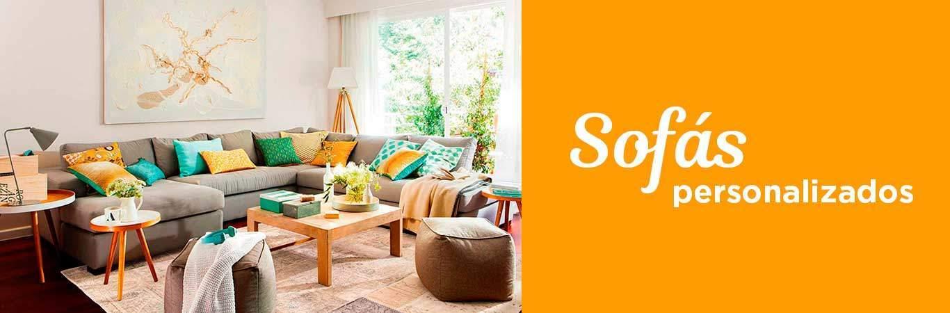 sofá a medida con cojines un pouf una mesa de centro en un living de un hogar